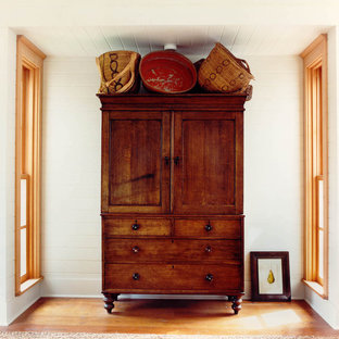 Diseño de dormitorio de estilo americano con paredes blancas y suelo de madera en tonos medios