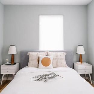 Modelo de habitación de invitados escandinava, pequeña, sin chimenea, con paredes grises y suelo de madera clara