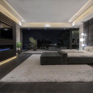 Ejemplo de dormitorio principal, minimalista, grande, con paredes blancas, suelo de madera oscura, chimenea lineal, marco de chimenea de baldosas y/o azulejos y suelo marrón