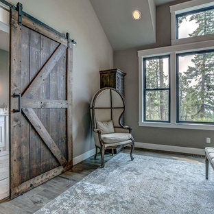 Inspiration for a large country master laminate floor and gray floor bedroom remodel in Other with gray walls