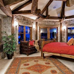 Imagen de habitación de invitados rústica, grande, con paredes marrones, suelo de travertino, chimenea tradicional, marco de chimenea de piedra y suelo beige