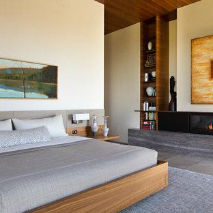 Пример оригинального дизайна: большая хозяйская спальня в современном стиле с бежевыми стенами, горизонтальным камином, фасадом камина из дерева, серым полом и деревянным потолком