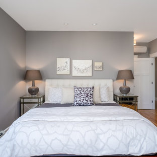 Mid-sized transitional master medium tone wood floor and brown floor bedroom photo in Portland Maine with gray walls