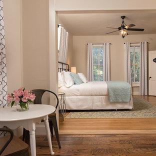 Foto de habitación de invitados de estilo de casa de campo, pequeña, con paredes beige, suelo de madera clara, chimenea tradicional, marco de chimenea de piedra y suelo marrón