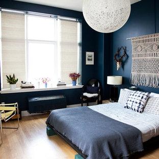 Modelo de dormitorio principal, moderno, grande, con paredes azules y suelo de madera clara