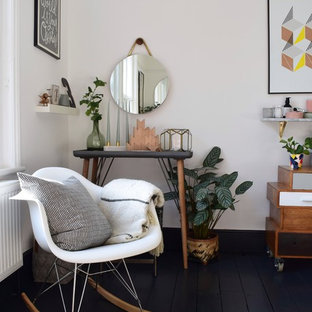 Design ideas for a large scandinavian master bedroom in London with white walls, painted wood floors, a two-sided fireplace, a metal fireplace surround and black floor.