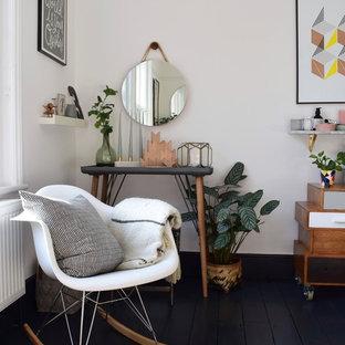 Diseño de dormitorio principal, escandinavo, grande, con paredes blancas, suelo de madera pintada, chimenea de doble cara, marco de chimenea de metal y suelo negro