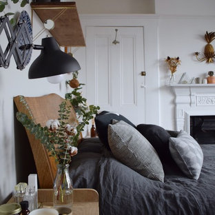 Modelo de dormitorio principal, escandinavo, grande, con paredes blancas, suelo de madera pintada, chimenea de doble cara, marco de chimenea de metal y suelo negro