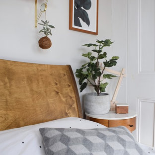 ロンドンの大きい北欧スタイルのおしゃれな主寝室 (白い壁、塗装フローリング、両方向型暖炉、金属の暖炉まわり、黒い床) のインテリア