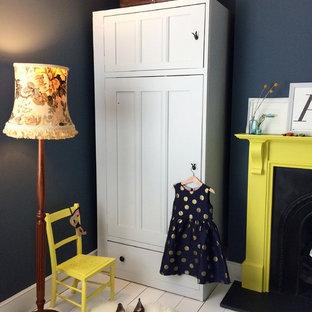 Modelo de dormitorio clásico renovado, de tamaño medio, con paredes azules, suelo de madera pintada, chimenea tradicional, marco de chimenea de madera y suelo blanco