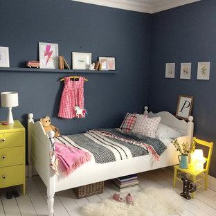 ロンドンの中サイズのトランジショナルスタイルのおしゃれな寝室 (青い壁、塗装フローリング、標準型暖炉、木材の暖炉まわり、白い床) のレイアウト