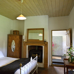 Example of a farmhouse bedroom design in Adelaide with white walls and a standard fireplace