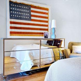 Imagen de dormitorio contemporáneo con paredes blancas y suelo de madera en tonos medios