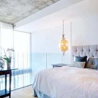 Ejemplo de dormitorio tipo loft, contemporáneo, sin chimenea, con paredes blancas y suelo de madera clara