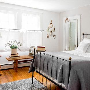 Imagen de dormitorio tradicional con paredes grises, suelo de madera en tonos medios y suelo naranja