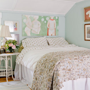 Example of a small cottage chic medium tone wood floor bedroom design in New York with blue walls