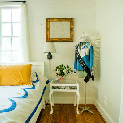 Example of a country medium tone wood floor and brown floor bedroom design in Austin with white walls