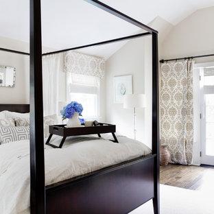 Traditional bedroom in New York with beige walls and dark hardwood floors.