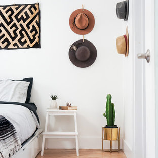 Example of an eclectic light wood floor bedroom design in Los Angeles with white walls