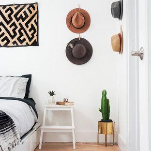 Ispirazione per una camera da letto boho chic con pareti bianche e parquet chiaro