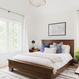 Example of a danish master vaulted ceiling bedroom design in Chicago with white walls