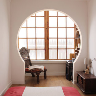 Eclectic medium tone wood floor bedroom photo in Tel Aviv with white walls