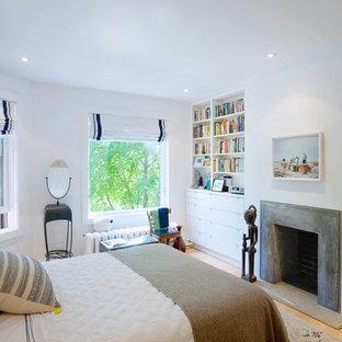 Diseño de dormitorio principal, escandinavo, de tamaño medio, con paredes blancas, suelo de madera clara, chimenea tradicional y marco de chimenea de hormigón