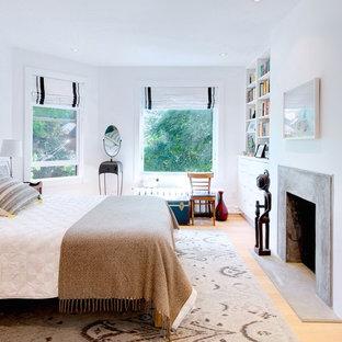 Ejemplo de dormitorio principal, nórdico, de tamaño medio, con paredes blancas, suelo de madera clara, chimenea tradicional y marco de chimenea de hormigón