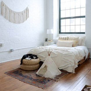 Bedroom - eclectic medium tone wood floor and brown floor bedroom idea in Providence with white walls