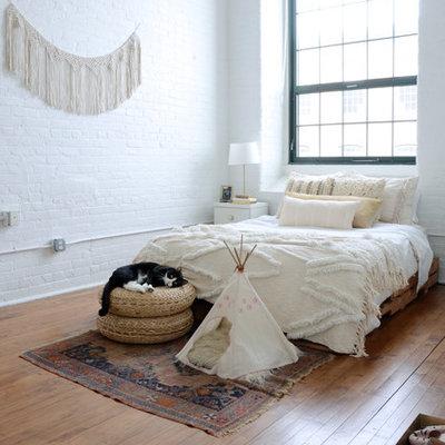Bedroom - eclectic medium tone wood floor and brown floor bedroom idea in Providence with white walls