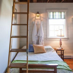 Immagine di una camera da letto costiera con pareti bianche, pavimento in legno massello medio e pavimento arancione