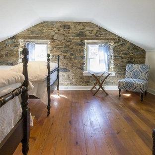 Modelo de habitación de invitados clásica, pequeña, con paredes negras, suelo de madera en tonos medios, chimenea lineal y suelo marrón