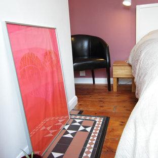 Imagen de dormitorio principal, bohemio, de tamaño medio, con paredes rosas, suelo de madera en tonos medios y marco de chimenea de baldosas y/o azulejos