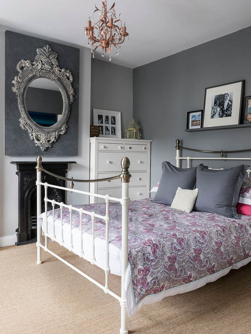Elegant carpeted bedroom photo in London with gray walls and a standard  fireplace