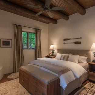 Idéer för ett amerikanskt huvudsovrum, med beige väggar, klinkergolv i terrakotta, en öppen hörnspis och en spiselkrans i gips