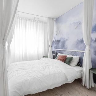 Example of a danish light wood floor and beige floor bedroom design in Other with white walls