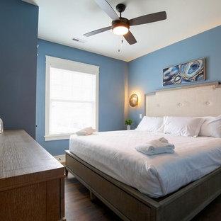Imagen de habitación de invitados costera, de tamaño medio, sin chimenea, con paredes azules, suelo de madera oscura y suelo verde