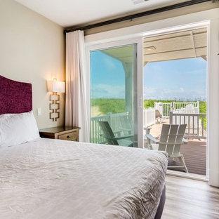 Foto de habitación de invitados marinera, pequeña, sin chimenea, con paredes beige, suelo vinílico y suelo marrón