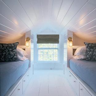 Ejemplo de habitación de invitados costera, pequeña, sin chimenea, con paredes blancas y suelo de madera pintada