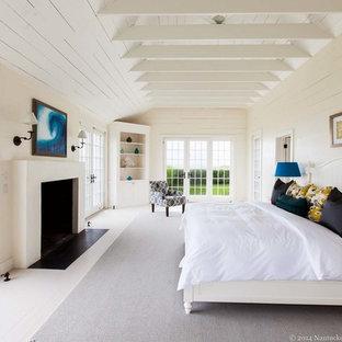 Immagine di una grande camera matrimoniale stile marino con pareti bianche, pavimento in legno verniciato, camino classico e cornice del camino in intonaco
