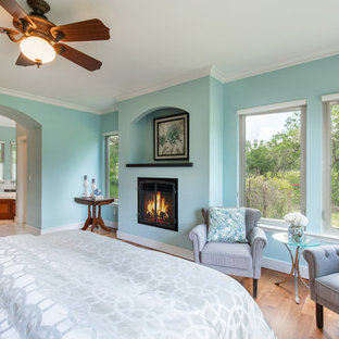 Inspiration for a mid-sized transitional master bedroom in Sacramento with green walls, medium hardwood floors, a standard fireplace, a plaster fireplace surround and brown floor.