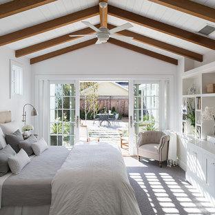 Modelo de dormitorio principal, de estilo de casa de campo, de tamaño medio, con paredes blancas y moqueta