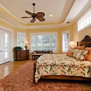Ejemplo de dormitorio principal, exótico, grande, con paredes amarillas