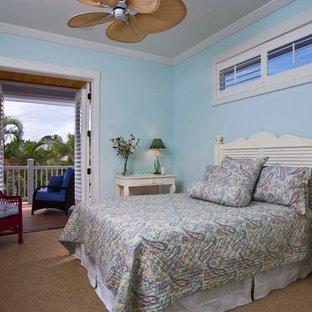Diseño de dormitorio tropical, sin chimenea, con paredes azules y moqueta