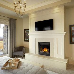 Modelo de dormitorio principal, tradicional renovado, grande, con paredes beige, suelo de baldosas de porcelana, chimenea tradicional, marco de chimenea de yeso y suelo beige