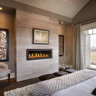 Inspiration pour une grand chambre parentale minimaliste avec un mur beige, un sol en bois foncé, une cheminée ribbon, un manteau de cheminée en carrelage et un sol marron.