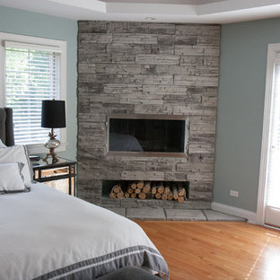 Small modern master bedroom in Chicago with blue walls, limestone floors, a corner fireplace, a stone fireplace surround and brown floor.