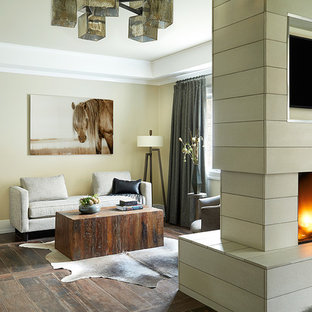 Design ideas for a large contemporary master bedroom in New York with beige walls, ceramic flooring, a two-sided fireplace and a concrete fireplace surround.
