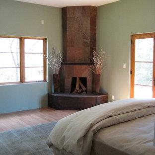 Ispirazione per una camera matrimoniale classica di medie dimensioni con pareti verdi, pavimento in bambù, camino ad angolo e cornice del camino piastrellata