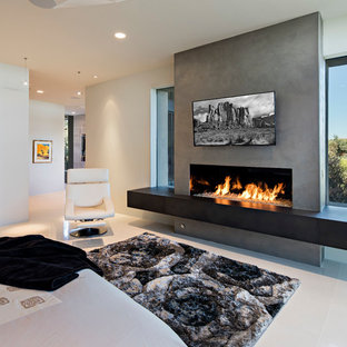 Photo of an expansive contemporary master bedroom in Phoenix with limestone floors, a ribbon fireplace, white floor, multi-coloured walls and a plaster fireplace surround.